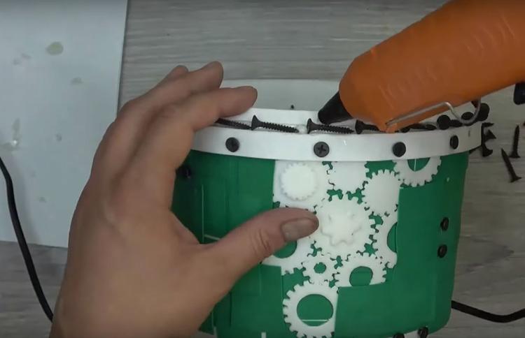 По верхнему краю кашпо на горячий клей закрепите саморезы или какие-то другие мелкие детали