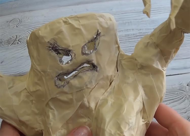 Придумайте рожицу пострашнее: обычно в выигрышном свете предстают раскосые глаза и кривой рот с опущенными уголками. Нарисуйте ее на заготовке и по контурами вырежьте ножницами с острыми кончиками