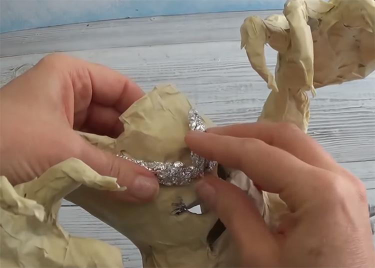 Последний штрих в каркасе – хмурые брови страшилы. Сформируйте их из фольги и прилепите скотчем