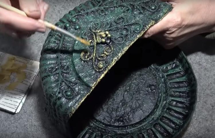 После двух предыдущих слоёв наносится золотая краска. Следует подчеркнуть все выступающие детали так, чтобы они заиграли, став более заметными. Золотом следует оттенить составляющие из верёвки, края и рельефные части конструкции