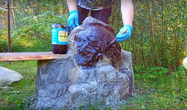 Всю поверхность валунов автор прокрасила смесью битума и лака. Такой состав защитит цемент от влаги и придаст ему натуральный, «каменный» вид. Можно сделать это кистью или распылителем