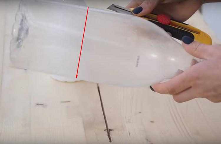 Разрез должен проходить примерно на расстоянии одной трети от общей длины тары. Старайтесь сделать край ровным. А вторую бутыль следует отрезать так, чтобы её граница при вкладывании бутылей одну в другую находилась вровень с краем большей бутылки. При этом, расстояние между крышками горлышек следует оставить не меньше 2 см