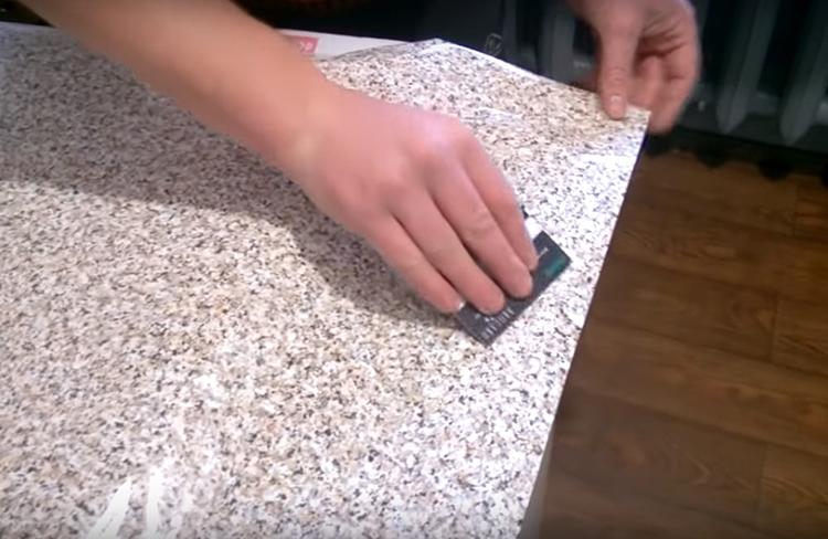 У плёнки нужно отогнуть край защитного слоя и дальше разглаживать её на основе, постепенно отодвигая защиту всё дальше, той же тряпкой или стеком. Можно использовать обычную пластиковую карту