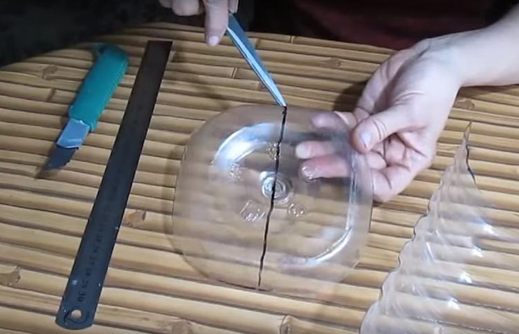 Чтобы зафиксировать края хлебницы, используем донышко бутыли. Его следует разрезать сначала ровно пополам, по линии маркера, а потом вырезать жёсткое дно серединки полукругом