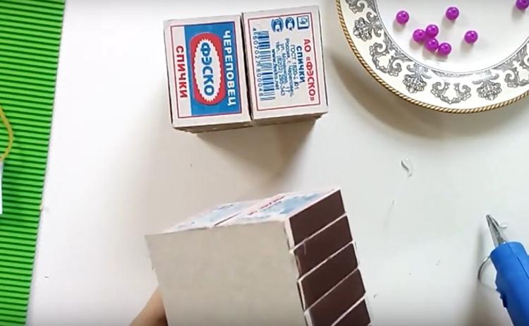 На одну из стенок нужно наклеить кусок картона, точно вырезанный по размеру. Клей в этом случае наносится на картонные рёбра коробков. Такая стенка нужна для того, чтобы подвижные части не проскакивали внутрь.