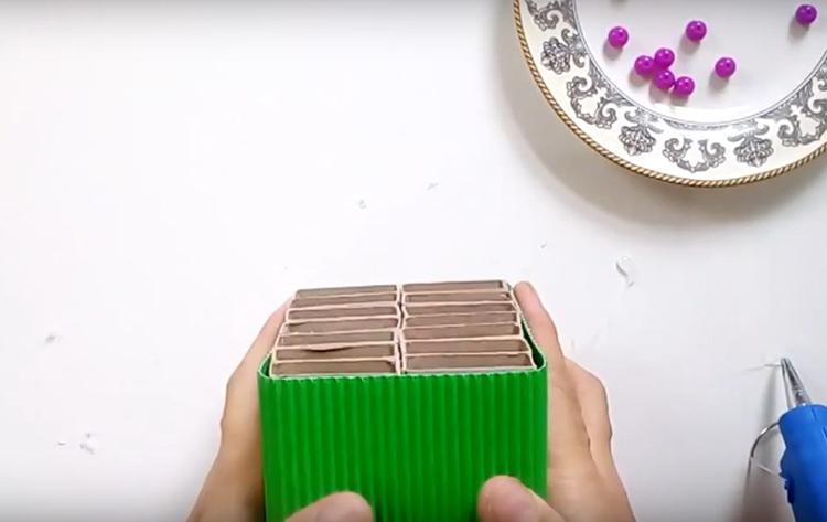 Автор использовал для оформления органайзера гофрированный тонкий картон. Им оборачивают органайзер и крепят на горячий клей по всей поверхности, особенно – по краям, чтобы картон не отставал на заметных местах