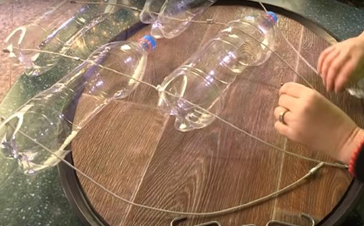Самая трудная в этой работе задача – правильно распределить все бутылки на равном расстоянии друг от друга. Разложите их на столе и до обжима скобок сначала выровняйте каждую так, чтобы в результате они уравновешивали друг друга. И только после полной расстановки зажмите закрепляющие скобки