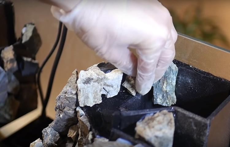 С помощью того же клея закрепите камни на каркасе как можно плотнее друг к другу, создавая естественные выступы и вершины