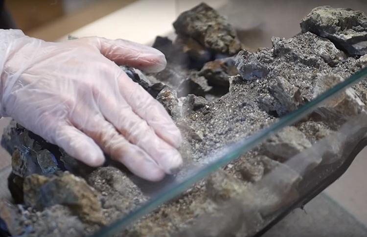 Пока силикон не высох, пальцами в перчатках примните песок, чтобы он хорошо приклеился, а после высыхания сметите излишки мягкой кистью