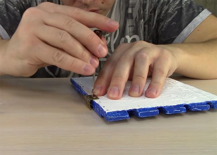 Чтобы закрепить крышку, используйте настоящие металлические петли, они будут отлично смотреться на имитации досок