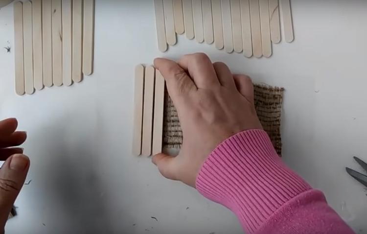 Приготовьте полоску джутовой мешковины и с помощью горячего клея наклейте на неё палочки в ряд