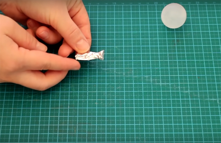 Сверните фольгу несколько раз и сформируйте из неё хвостик. Один кончик должен быть расплющен, а на втором нужно сделать выемку, чтобы она идеально стыковалась с окружностью шарика