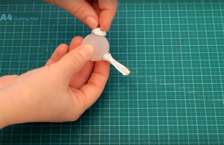 Приклейте обе детали из фольги к шарику с помощью клея «Момент». Не забудьте хорошо протереть и обезжирить основу перед этим. Для обезжиривания можно использовать обычную жидкость для снятия лака