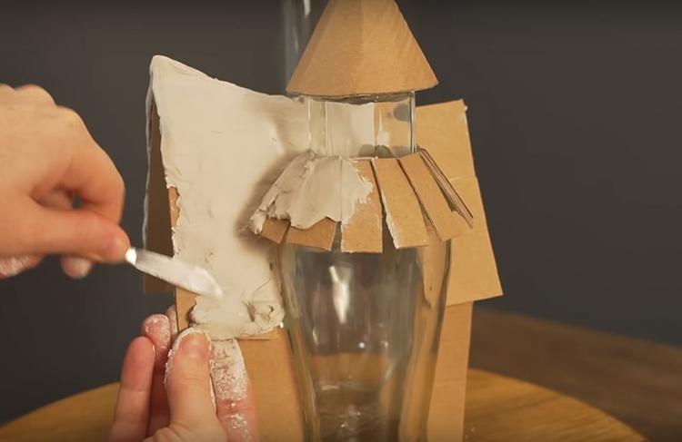 Покройте все части композиции слоем строительной шпаклёвки. Разведите её так, чтобы она была похожа на пластилин, добавьте для эластичности немного средства для мытья посуды. Шпаклёвку нужно наносить довольно быстро, она стремительно высыхает. Можно вместо неё взять замазку – её время высыхания дольше, а работать с ней проще, как с пластилином