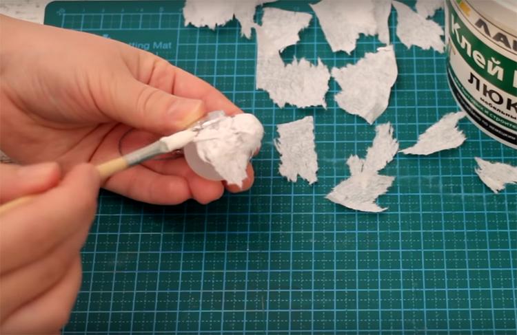 Порвите салфетку на мелкие клочки с неровными краями. Нанесите клей ПВА сначала на заготовку, потом приложите к ней кусочек салфетки, а по ней ещё раз пройдитесь кистью с клеем. Не старайтесь идеально растянуть бумагу по поверхности, ведь стоит задача сделать винтажную игрушку, а она должна выглядеть «взрослой»