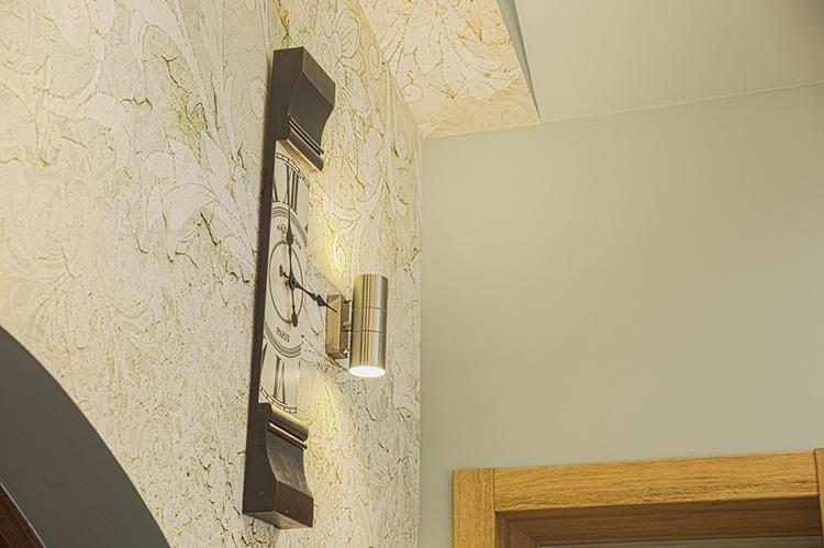 Необычные часы слегка разбавляют сдержанный и лаконичный интерьер спальниФОТО: escat.ru