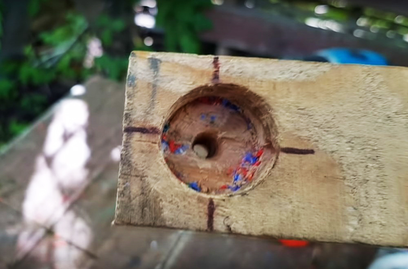 Для решения этой задачи Юрий приготовил вот такое простое приспособление. Оно представляет собой обрезок доски с углублением, соответствующим размерам крышки, и просверленными сквозными 4 отверстиями на высоте примерно в половину высоты крышки