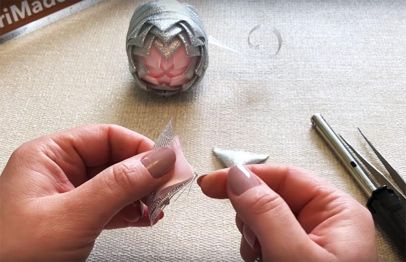 Чтобы сформировать ушки, возьмите треугольники серебристого и, меньший по размеру, розового цвета