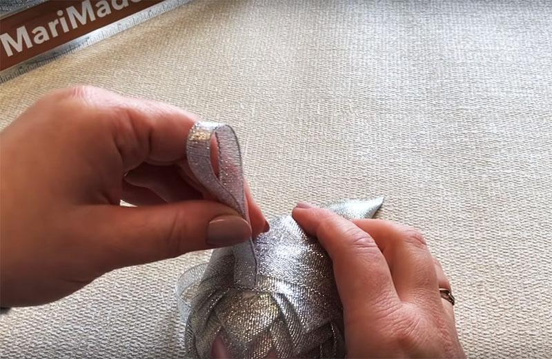 Закрепите на «экваторе» петлю для того, чтобы можно было повесить шарик на ёлку. Петлю сделайте из узкой ленты, а для фиксации используйте горячий клей