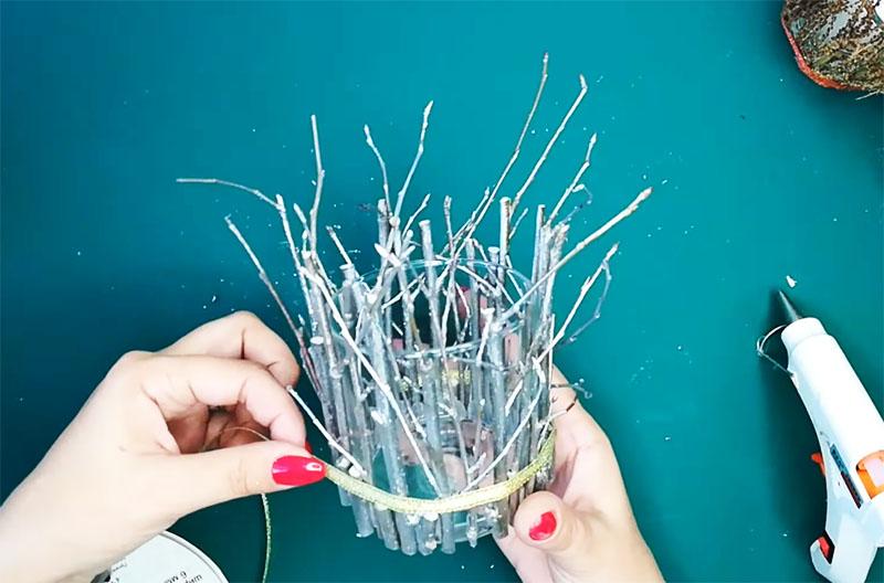 Когда все ветки займут свои места, снова закрепите ленту или верёвку по низу стакана
