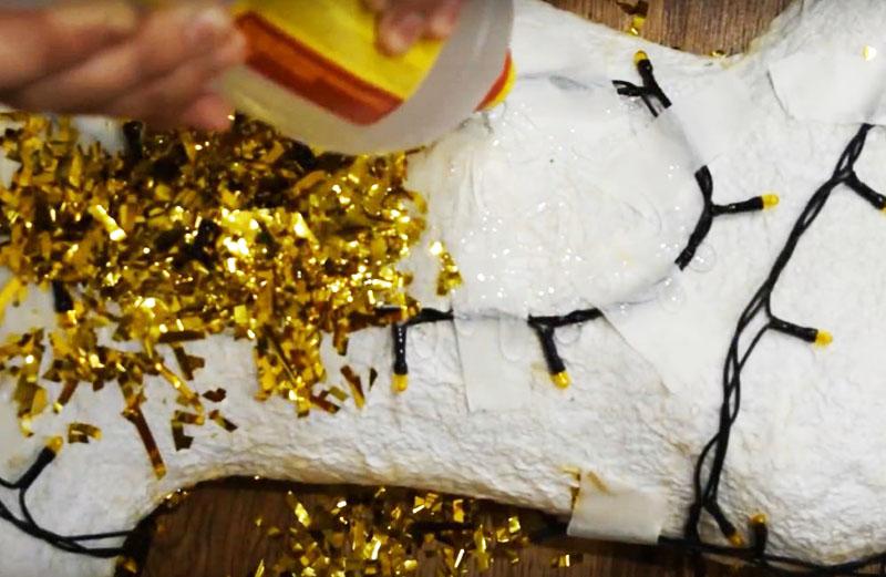 Чтобы имитировать шерсть, используйте золотой дождик. Нарежьте его на кусочки и приклейте, обмазывая фигуру клеем ПВА и накладывая стриженый дождик прямо сверху на гирлянду