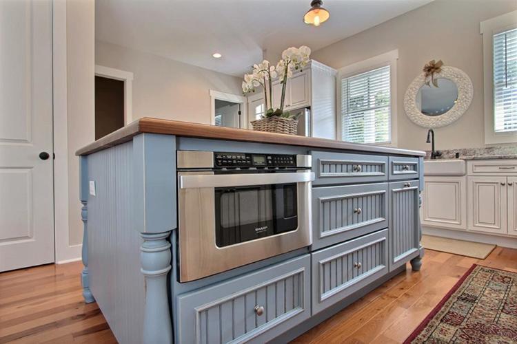 Если разместить такой гарнитур еще на стадии ремонтных работ, в «остров» можно вписать не только печь, но и посудомоечную машину