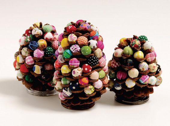 Если вам удалось раздобыть крупные кедровые шишки, то они могут стать украшением новогоднего стола. Декорируйте их маленькими конфетами драже