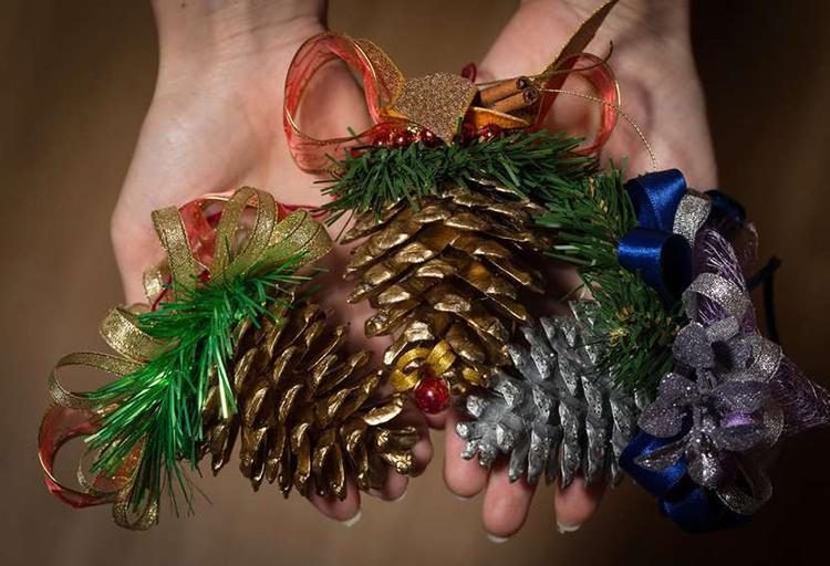 Крупные шишки, покрашенные блёстками и оформленные лентами можно повесить вместо шаров