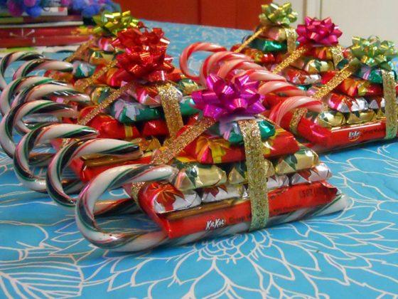 Замечательная идея для подарков, если на новогодней вечеринке будет много детворы. Основу саней составляют леденцы палочки, на них последовательно крепится большая плитка шоколада и конфеты . Вся композиция перевязывается лентой