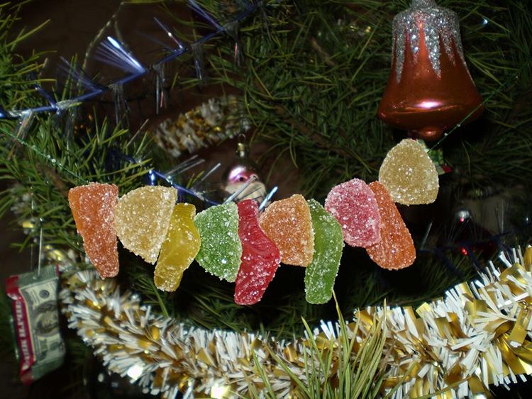 Ёлочные бусы можно изготовить из лески и мармелада. Просто нанизайте бусины на леску и подвесьте к ёлке. Мармелад немного подсохнет за время праздника, но это почти никак не скажется на его вкусовых качествах.