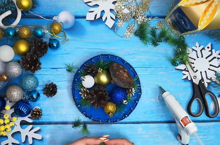 Декорируйте основание ёлочными украшениями. Используйте шишки и шарики, кусочки еловых веток, другие природные материалы