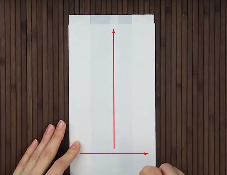 Сложите лист бумаги в полосу, загнув по краям, а потом пополам. Нанесите клей по линиям, указанным стрелками