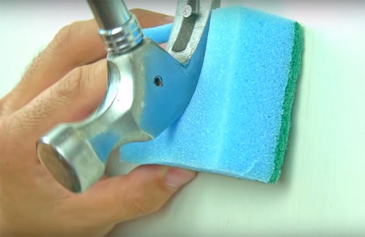Подложите под молоток обычную поролоновую губку для мытья посуды и смело выдёргивайте гвоздь. Поролон защитит стену от чрезмерного давления жёсткой части инструмента
