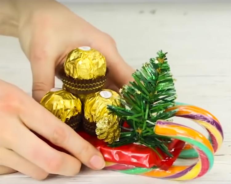 На санки на горячий клей или двусторонний скотч зафиксируйте конфеты и какую-нибудь игрушку