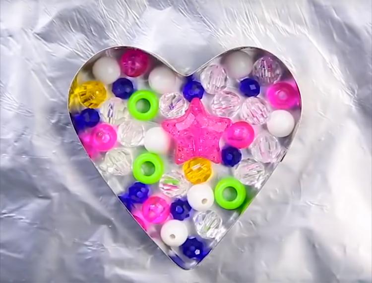 Уложите одним слоем пластиковую мелочь. Подбирайте самые яркие бусины и пуговицы, так получится интереснее