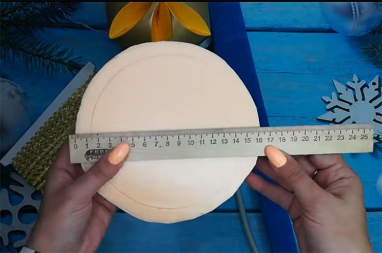 В качестве основания вам нужно подготовить круглую картонную коробку. Просто сделайте два круга диаметром примерно 16 см и склейте их между собой полоской такого же картона. Как альтернативный вариант – используйте кусок пеноплекса, вырезанный в форме круга