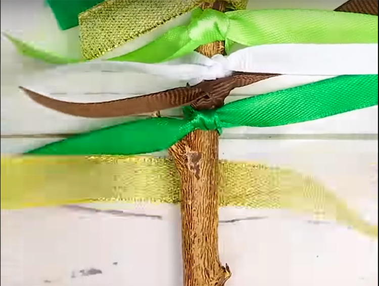 Завяжите разные по цвету ленты на два узелка на ветке так, чтобы концы торчали в стороны