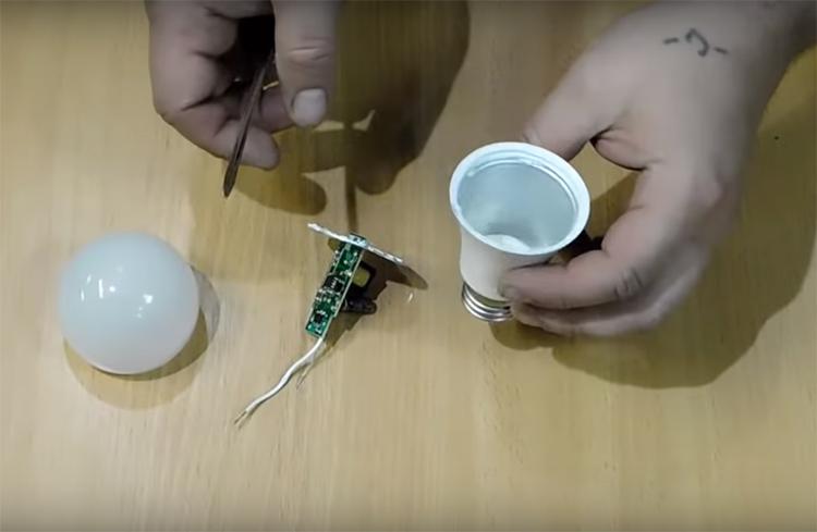 Плату с проводами, соединяющими её с патроном, нужно удалить из корпуса лампочки. Вся эта начинка вам больше уже не пригодится, так что можно отправить её в мусорное ведро без особых сожалений