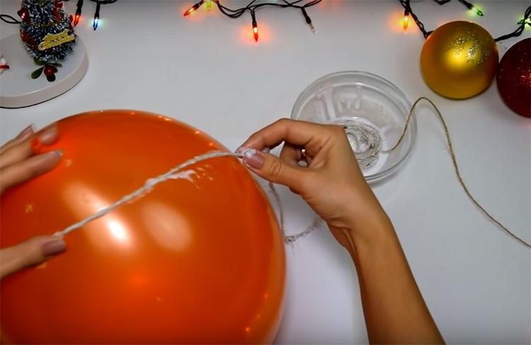 Смочите нитку в разбавленном водой клее и намотайте её на надутый шар. Нитку не обрезайте, работайте со всем мотком, пока он не закончится