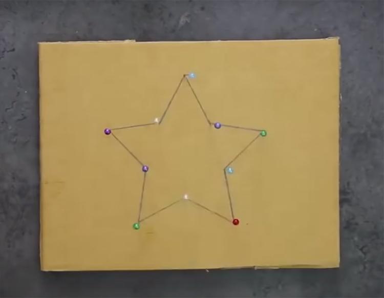 На кусочке картона нарисуйте звезду и закрепите в вершинах лучей булавки