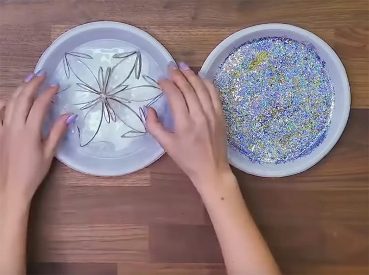 Приготовьте неглубокую тарелку с клеем или домашним клейстером, который можно приготовить самостоятельно, и такую же тарелку с блёстками. Диаметр тарелок должен быть таким, чтобы снежинка полностью в них помещалась. А дальше всё просто: обмакните снежинку из картона сначала в клей, а потом – в блёски