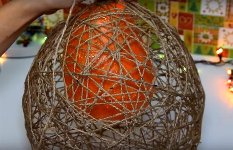 Когда форма полностью застынет, можно проколоть шарик и извлечь его из заготовки. Если всё сделано правильно, нитки сохранят свою форму