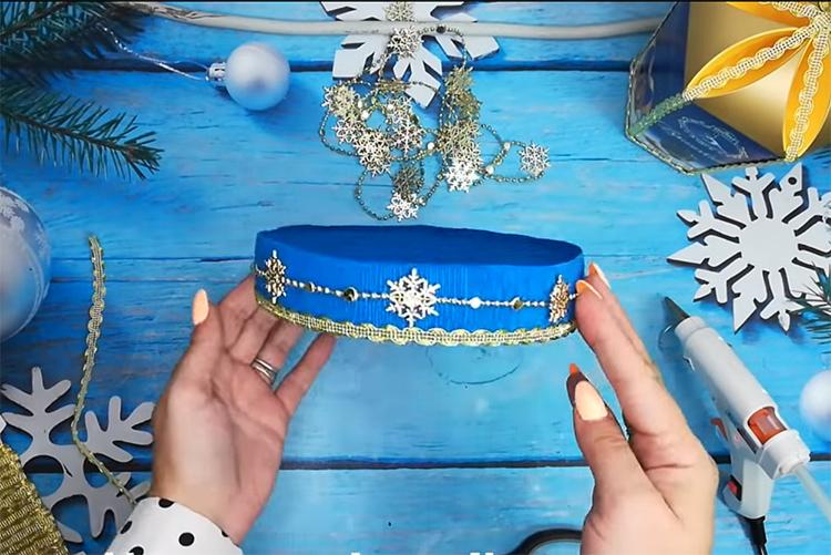 Основание для подарка нужно декорировать. Используйте по бортику тесьму и мишуру, ёлочные бусы. Все это крепится горячим клеем. Можно использовать бусины или стразы, картинки из новогодних открыток