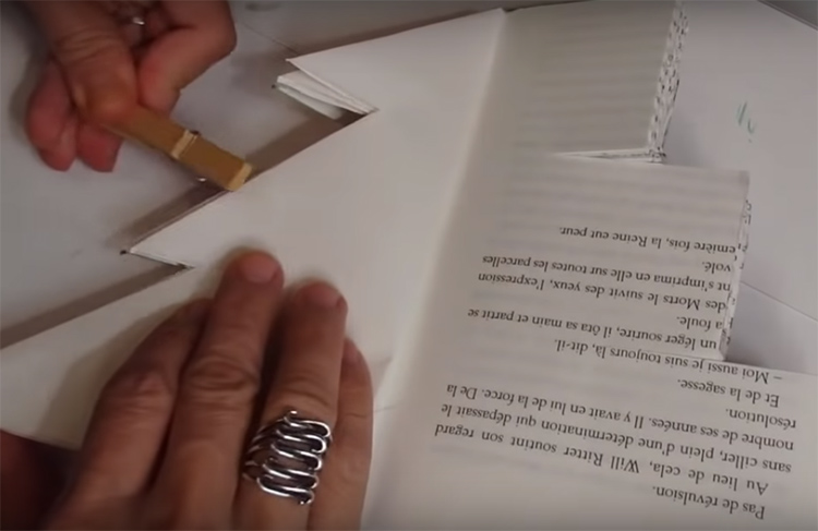 Нужно загнуть таким образом все три яруса на странице. Чтобы книга не мешала вам и не раскрывалась постоянно во время работы, скрепите загнутые листы прищепкой или придавите чем-то тяжёлым