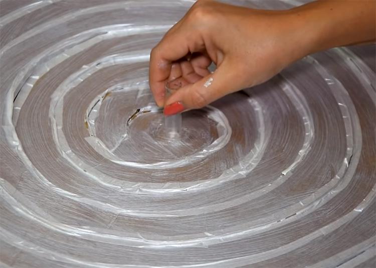 Нанесите клей и закрепите шприц по центру спирали острым концом в картоне. Для больше надёжности соединения можно залить по краям шприца горячий клей