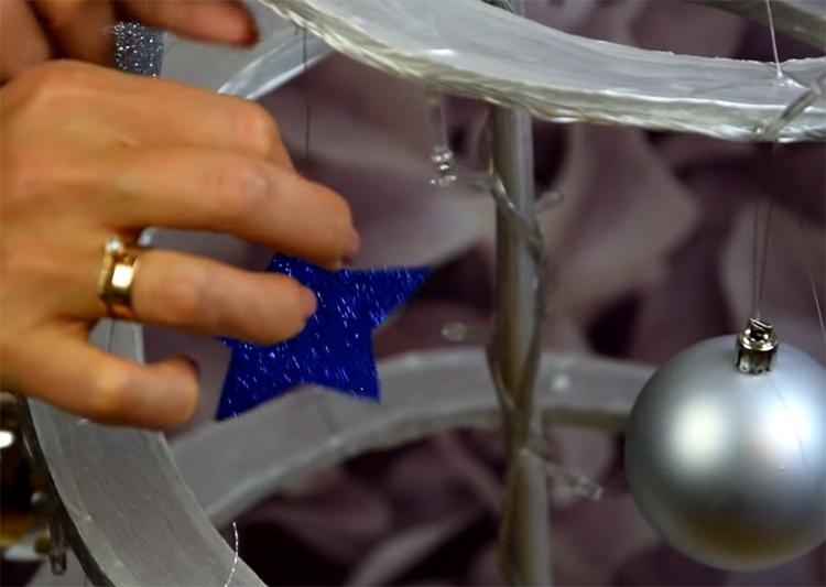Ёлочные украшения можно зафиксировать на картоне обычными скрепками. Повесьте шары и прочие украшения по всей длине спирали. Можно использовать ещё и яркую мишуру