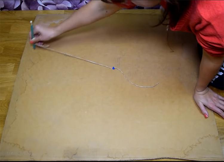 Закрепите кнопкой нитку в центре будущего круга, а к другому концу привяжите карандаш. Такая простая конструкция позволит вам провести линию на одинаковом удалении от центра и нарисовать правильный круг