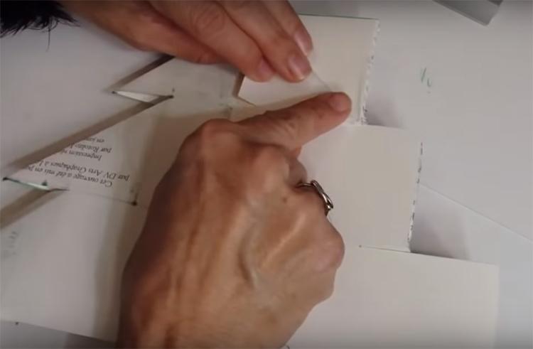 Когда вся книга уже разрезана, нужно сделать загибы на листах. Не обязательно на каждом, вы можете делать их на двух или трёх сразу. Загиб идёт наискосок от верхушки размеченного квадрата к краю, как показано на фото