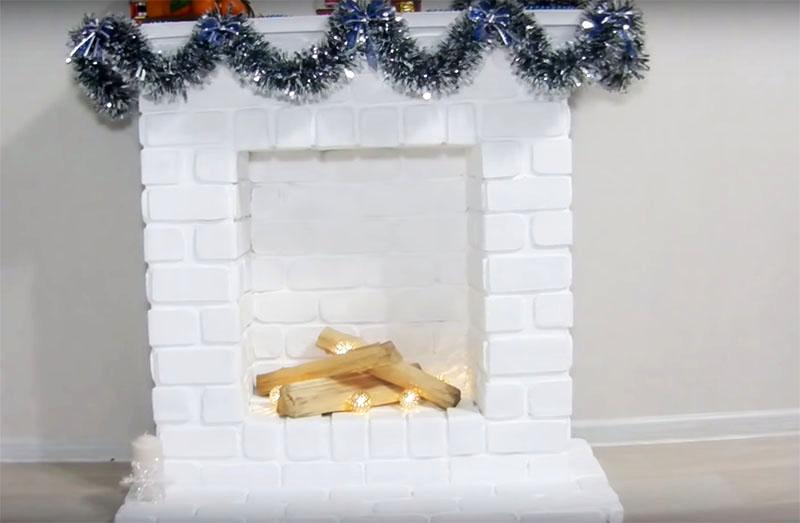 А когда вы создадите полную имитацию кирпичной кладки, можно добавить новогоднего декора. Украсьте камин мишурой, повесьте на него традиционные носки, а в топку положите поленья и мерцающую светодиодную гирлянду