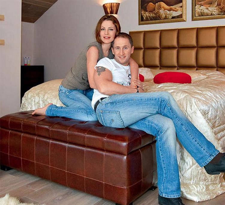 Кровать украшает роскошное шёлковое покрывало цвета слоновой кости и несколько красных декоративных подушек
